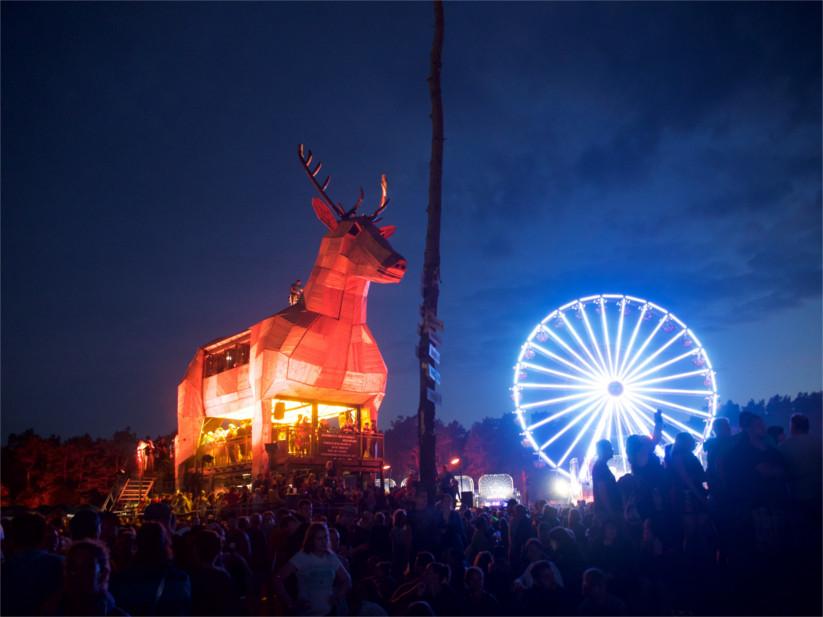 Der beleuchtete Platzhirsch bei Nacht zusammen mit dem Riesenrad